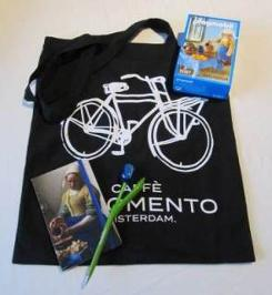 """""""Art-related, Dutch goodies"""" prize package, includes: – Playmobil toy of Vermeer's The Milkmaid (from the Rijksmuseum) – A notebook featuring Vermeer's The Milkmaid on the cover – A tulip pen – A fabric bag from a local Amsterdam cafe"""