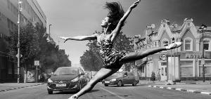 A girl is jumping like a ballet dancer in front of vehicles