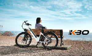 girl sitting on bench overlooking beach, bike propped up behind bench