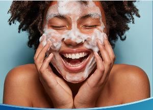 girl with foam on face, smiling