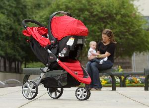 Mom and baby in background behind red and black Britax B-Agile travel system