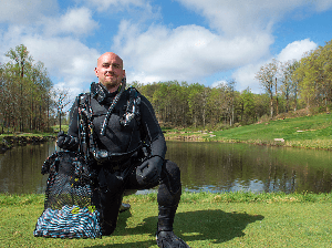 scuba diver holding a bag of golf balls