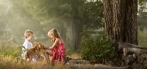 Two Children and a dog playing in woods photography