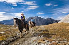 Two people riding in the mountains.